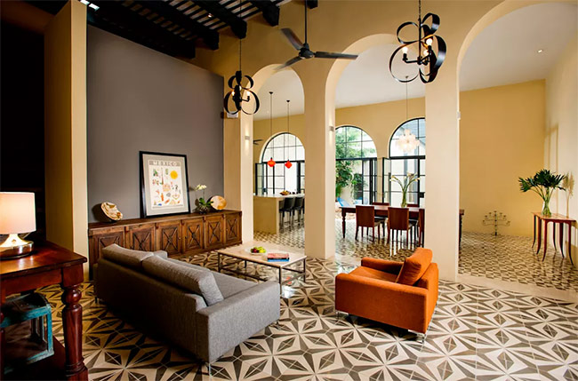 Sự mộc mạc có thể thấy qua độ thô ráp của trần nhà, các trụ cột, và gạch trang trí. Bộ ghế sofa hiện đại khiến căn phòng trở nên gần gũi và tạo sự mới mẻ cho một cuộc gặp gỡ bạn bè nơi đây.
