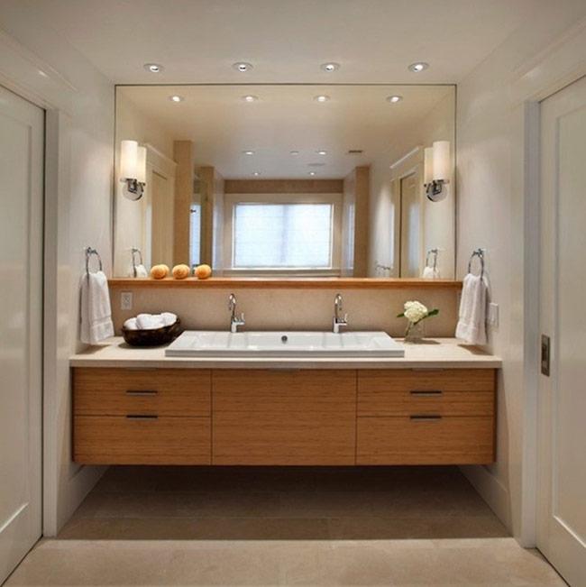 Vòi hoa sen được sử dụng rộng rãi do tiết kiệm nước khi so sánh với bồn tắm. Trung bình 1 lần tắm dùng 80 lít nước nếu dùng vòi hoa sen, trong khi đó bồn tắm dùng 150 lít. 3. Gương và kệ Trong phòng tắm, bạn không thể bố trí thiếu gương và kệ. Gương không còn giới hạn chỉ là một miếng kính được cắt nhỏ vừa tầm để soi mặt mà nội thất phòng tắm đã dường như trở thành nội thất của các shop thời trang, spa với những mảng gương phá cách, rất to và dài, chiếm trọn hết cả chiều ngang phòng tắm.