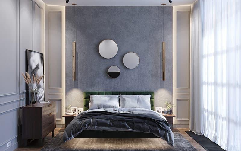 Bên trong phòng ngủ chính, ba tấm gương trang trí nổi lên một bức tường đầu giường màu xám.