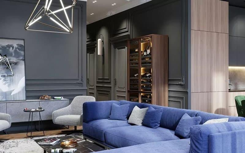 Bức tường lớn màu xám trong phòng khách, cung cấp một cái nhìn cổ điển cho cảnh quan hiện đại. Một tủ lưu trữ rượu vang được chiếu sáng làm nổi bật sự sang trọng, những chai rượu trở thành một tác phẩm nghệ thuật nổi bật trong phòng.