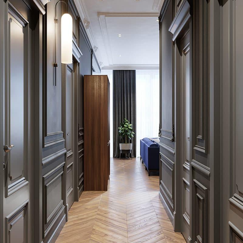 Sàn gỗ xương cá trở lại bên trong hành lang của ngôi nhà, dẫn đến phòng ngủ và phòng tắm. Cùng một sàn gỗ chạy khắp tất cả các khu vực chung của ngôi nhà, tạo sự ấm áp bên cạnh bức tường đúc màu xám. Một chiếc đèn treo tường tân cổ điển chiếu sáng dọc hành lang.