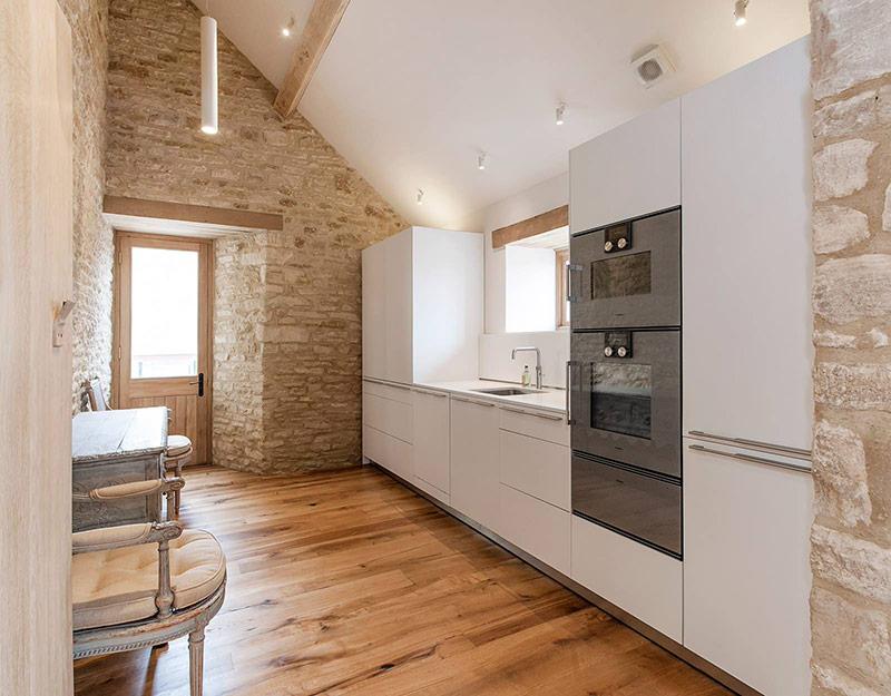 Có thể là bạn muốn những chiếc tủ kiểu dáng đơn giản để không gian bếp trông thật sạch sẽ. Đây là một sự lựa chọn phổ biến và nó có thể được sử dụng để làm nổi bật lên một khía cạnh khác trong nhà bếp của bạn, giống như trong bức hình này, bức tường đá hoàn toàn thu hút ánh nhìn so với tủ bếp trắng.